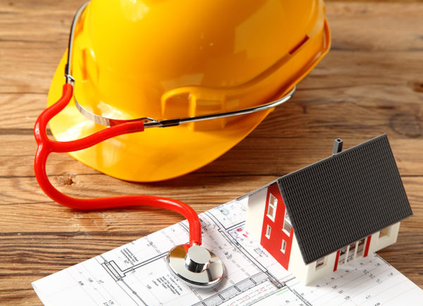 Yellow hardhat wearing a stethoscope checking a home