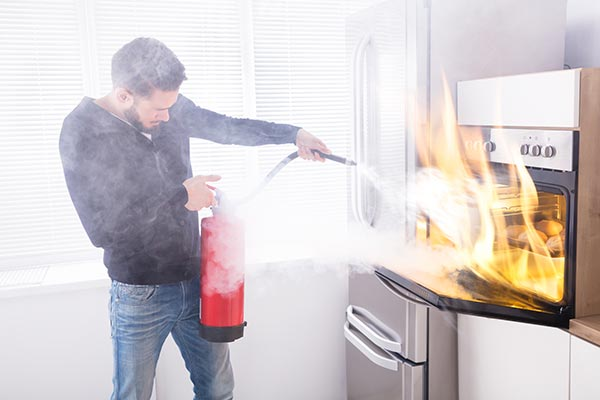 man-with-fire-extinguisher putting out a fire